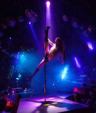 This picture taken on July 2, 2012 shows pole dancing teacher Wang Jing performing at a nightclub in southwest China's Chongqing municipality. A nightclub activity mostly considered the domain of strippers in the United States, pole dancing with clothes kept on is nudging its way into the mainstream Chinese exercise market with increasing numbers of gyms and dance schools offering classes. CHINA OUT AFP PHOTO (Photo credit should read STR/AFP/GettyImages)